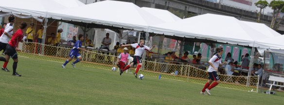 In the background, we can see additional match officials with flag during Deaflympic competition.